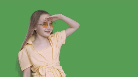 para a frente : Girl teenager looking far away on transparent background. Young girl in yellow glasses and dress peering into distance. Alpha channel, keyed green screen