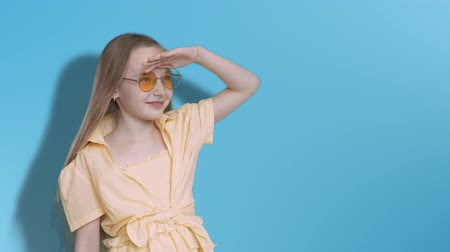 looking far away : Girl teenager looking far away on blue background in studio. Young girl in yellow glasses and dress peering into distance on blue wall background Stock Footage