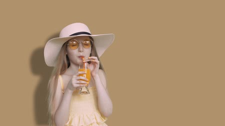 hidrasyon : Girl teenager drinking orange juice by straw from glass on beige wall background. Young girl in sunglasses and hat drinking orange fresh in studio