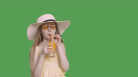 hidrasyon : Girl teenager drinking orange juice by straw from glass on transparent green background. Young girl in yellow glasses and hat drinking cocktail on green background. Alpha channel, keyed green screen Stok Video
