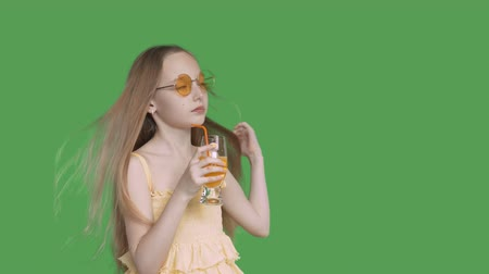 relax : Teenager girl drinking orange juice by straw from glass on transparent green background. Young girl enjoying fresh orange cocktail on green background. Alpha channel, keyed green screen