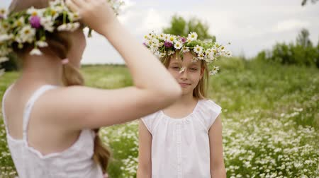 margarida : Girls are playing together. Teen girl puts wreath to her friend head walking at flower meadow at summer. They wearing white dresses. Portrait of girl smiling at camera. Children friendship.