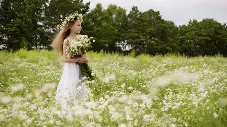 csavarkulcs : Girl is standing on flower glade looking at camera and smiling. Cute teen girl in white dress with wreath on head and bouquet of daisies at flower meadow. She is posing at shoot. Windy summer day. Stock mozgókép