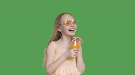 tenso : Summer vacation style. Laughing teen girl in yellow glasses and dress drinking orange juice by straw from glass on transparent green background. Alpha channel, keyed green screen. Happy childhood. Vídeos