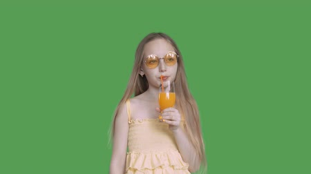 szalma : Thoughtful girl in yellow sunglasses and dress is drinking orange juice by straw from glass on transparent green background. Resting on summer vacation concept. Alpha channel, keyed green screen.