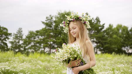 csavarkulcs : Portrait of beautiful girl is standing on flower glade with closed eyes. Cute teen girl in white dress with wreath on head and bouquet of daisies at flower meadow. Windy summer day.
