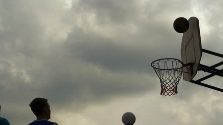 abroncs : Sportsman throwing basketball ball in hoop outdoor. Basketball player throwing ball in ring on sport ground. Basketball score slow motion