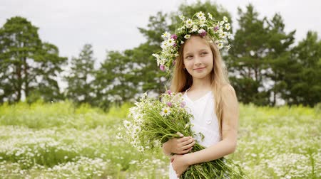 kamilla : Smiling girl in floral wreath with chamomile bouquet summer field. Portrait girl teenager with flower bouquet posing on camomile field at summer day
