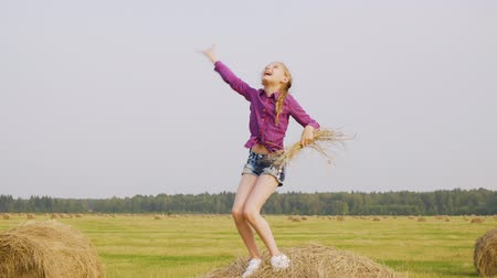 heuhaufen : Playful girl dancing on hay stack with straw in hands at harvesting field. Cheerful teenager girl having fun on haystack