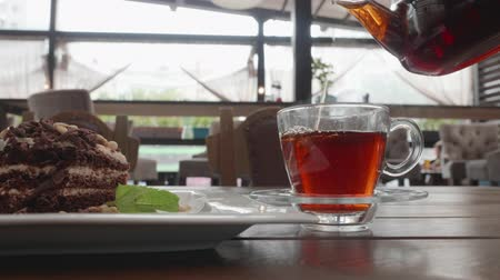 pastelaria : Pouring rich tea in glass cup from in transparent teapot on cafe table. Tea glass and chocolate pie on wooden table in summer cafe. Tea drinking in confectionery shop