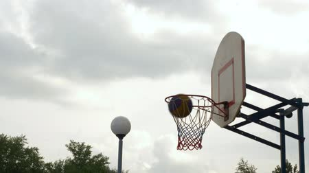 abroncs : Throwing the ball into basketball hoop outdoor. Basketball player throwing ball in ring on sport ground. Basketball goal slow motion Stock mozgókép