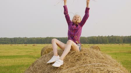 hay pile : Carefree teenager girl scattering dry straw on countryside field. Happy girl teenager sitting on hay stack. Young girl having fun on autumn harvesting field