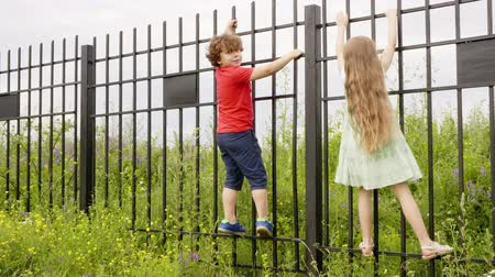 proibir : Little boy and girl climbing on iron fence in countryside. Playful childrens having fun in village at summer vacation Vídeos