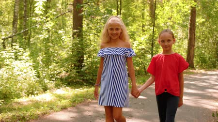 schattig : Two Pretty Smile Girls Walk Hold Hands Summer Park. Couple Happy Caucasian Female Children Stroll Asphalt Road Wood Trees Summertime. Leisure Activity Casual Clothes Free Time Holiday Concept