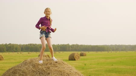 palheiro : Pretty Girl Dance Haystack Mow Crop Straw Coil. Happy Caucasian Child Musical Movements Hay Bale Top. Cute Blonde Teenage Casual Clothes Summertime Harvest Farm Field Landscape Distant Wood Background