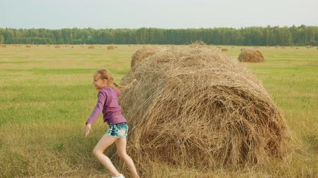 tondre : Girl Run Climb Haystack Straw Coil Harvest Time. Happy Caucasian Friends Have Fun Mow Wheat Field Ground Summertime. Paysage agricole de cultures lointaines sur fond de forêt lointaine Concept agricole