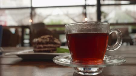 koflík na čaj : Tea time in cafe in rainy weather. Cup of hot tea with smoke in transparent cup on saucer in cold room. Piece of chocolate cake on the background. Dessert at the restaurant terrace. Dostupné videozáznamy