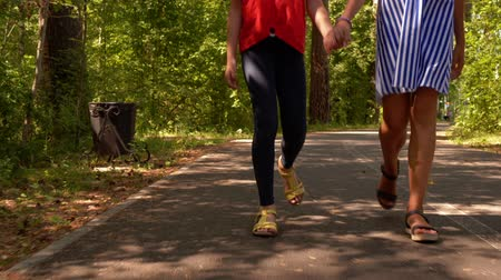 kalhoty : Childrens friendship and leisure in summer vacations. Two teens girls friend walking in park together holding hands, legs closeup. They are going on asphalt path among green forest. Dostupné videozáznamy