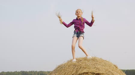 balé : Harvesting field. Teen girl is dancing with straw in her hands standing on hay stack in countryside. Happy childhood in rural area village at summer vacations. Living in farm.