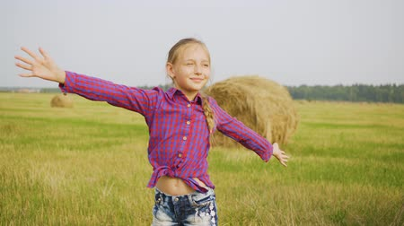 hay fields : Summer vacation in village, countryside, rural area. Happy freedom teen girl on harvesting field enjoys nature on farm harvesting. She stands with her arms out to the side.