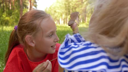 razem : Happy childhood and outdoor activities. Two playful teen girls lies on grass and having a fun in nature park together. Girl is eating grass and talking with her friend. Children friendship.