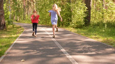 kalhoty : Happy childhood and outdoor activities at summer vacations. Teen girls friends playing running jumping in nature park on asphalt walkway, back view. They are playing games together. Dostupné videozáznamy