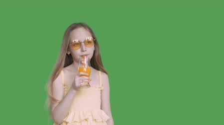 tenso : Young girl drinking orange juice from glass by straw on green background. Teenager girl drinking fruit cocktail on transparent green background. Alpha channel, keyed green screen Vídeos