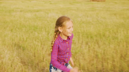 palheiro : Cheerful girl running to haystack at yellow meadow. Playful girl teenager climbing on hay stack on harvesting field. Autumn fun outdoor Stock Footage