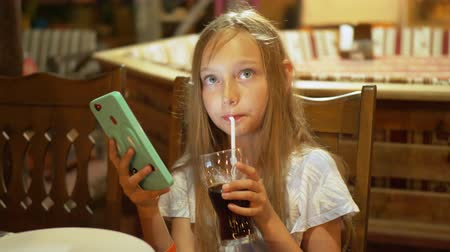 szomjúság : Teenager girl drinking from glass fizzy water and looking smartphone. Young girl drinking soda using mobile phone. Portrait agree girl swaying head Stock mozgókép