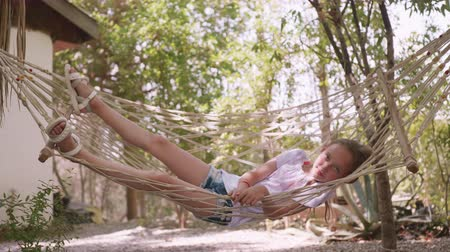 hamak : Relaxing girl swinging in hammock at summer vacation. Teenager girl relaxing in hammock in summer garden on trees landscape