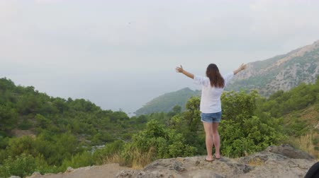 uzanmış : Tourist woman standing on mountain edge with stretching hands. Traveling woman raised hands on green hills landscape. Woman enjoying foggy mountain landscape Stok Video