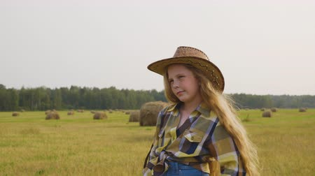 szénaboglya : Cowgirl on countryside field on haystack background. Young cow girl in hat posing front camera. Country girl in checkered shirt on harvesting field in village