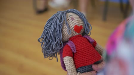 knitted : Aged hands holding knitted doll. Close up female hands of elderly grandmother holding handmade doll Stock Footage