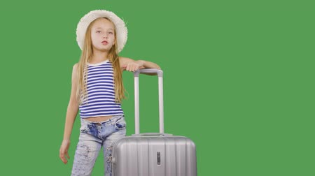 subscribers : Tourist girl gesturing hello with hand to followers and talking on green background. Girl teenager with suitcase speaking with subscribers in social networks. Alpha channel, keyed green screen