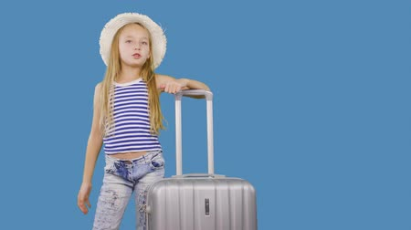 subscriber : Traveling girl with suitcase greeting and gesturing hello on blue background in studio. Girl teenager with suitcase speaking with subscribers in social networks on blue wall background