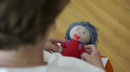 popje : Senior woman holding knitted doll in hands. Close up female hands of elderly grandmother holding handmade doll