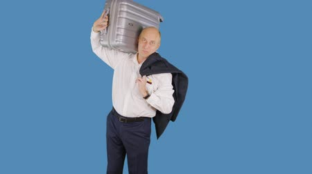 schouder : Tourist man taking to shoulders travel suitcase on blue background. Man in business suit holding suitcase on shoulders on blue wall background in studio