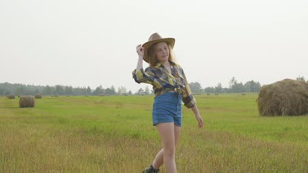 hooiberg : Country Style Little Girl Walking on Green Field. Summer Countryside Vacation. Caucasian Young Lady in Cowboy Straw Hat. Blond Farmer Teenage Daughter with Freckles on Haystack Landscape Stockvideo