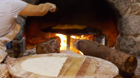 remo : Gezleme Bread Cooked in Traditional Turkish Stove. National Food Cooking. Woman Hand Turned over Cake with Wooden Spatula. Pita in Old Stone Glowing Oven. Home Bakery or Bakehouse Concept Filmati Stock