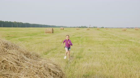 palheiro : Happy Little Girl Running on Sunny Haystack Field. Blond Cheerful Kid Try to Climb on Stack of Yellow Hay Straw. Active Beautiful Child Spend Time on Countryside. Rural Summer Vacation