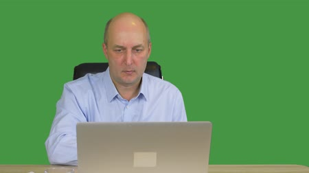 tenso : Businessman working on laptop in office on green background. Focused businessman showing index finger. Attentive and serious worker. Alpha channel, keyed green screen Vídeos