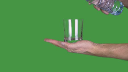 tenso : Male hand holding empty glass on green background. Man pouring water from plastic bottle to glassful on transparent green background. Alpha channel, keyed green screen Vídeos