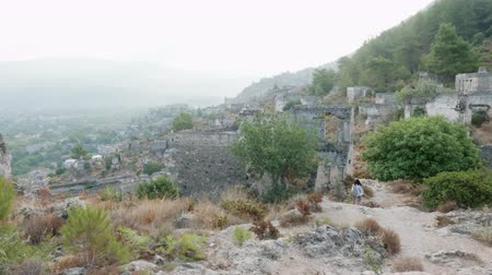 medeniyet : Tourist woman walking along ruined buildings in old mountain town. Traveling woman going on trail in ancient city on foggy mountain. Cloudy city landscape from cliff Stok Video