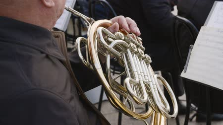 orkiestra : Close up man playing on french horn on city street. Street musician play music on wind instrument. Outdoor performance acoustic instrumental band