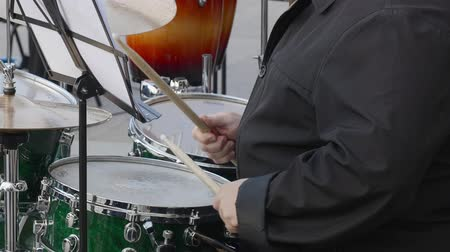 bicí nástroje : Drummer plays music on drums kit outdoor. Close up drummer hand with drumstick playing drum set and plate on concert. Musical performance on city street