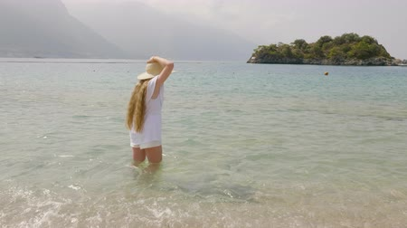 sombrero de paja : Long haired girl in straw hat and white clothes standing in transparent sea water on mountain background. Tourist girl in sea water on mountain silhouettes in horizon