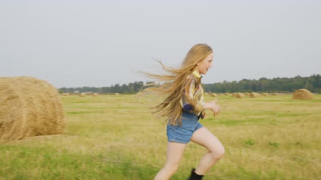 szalma : Teenager girl running on harvesting field on hay stack landscape in autumn village. Cheerful girl in jeans short and checkered shirt running on countryside field Stock mozgókép