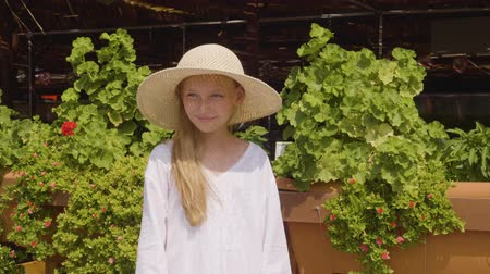 vidět : Portrait teenager girl in straw hat at sunny day in resort hotel. Smiling girl teenager in summer hat standing on green plants on cafe facade in resort