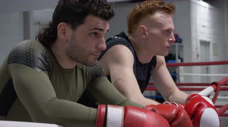 atleta : Two boxer in boxing gloves resting after training on ring rope in fight club. Tired fighter relaxing after sparing on boxing ring in fitness club. Profile portrait athlete man Stock Footage