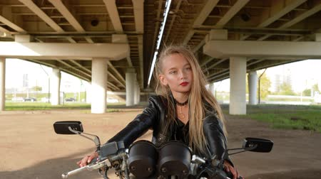 korhadt : Biker girl in black leather jacket sitting on motorcycle under car bridge. Rock girl posing on motorbike on urban landscape. Street fashion look modern youth